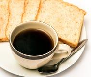 Kaffe och bröd indikerar morgonmål och svart royaltyfri bild