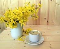 Kaffe och bukett av forsythia Royaltyfria Foton