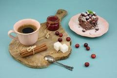 Kaffe- och chokladkaka med tranbärdriftstopp och kanel på träbräde, över turkosbakgrund Royaltyfri Fotografi