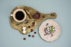 Kaffe- och chokladkaka med tranbärdriftstopp och kanel på träbräde, över turkosbakgrund Top beskådar Arkivbild