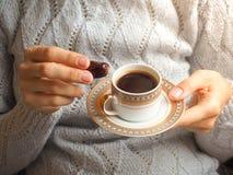 Kaffe och daterar En kopp kaffe i hennes händer med de arabiska data Fotografering för Bildbyråer