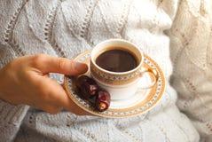 Kaffe och daterar En kopp kaffe i hennes händer med de arabiska data Arkivbilder
