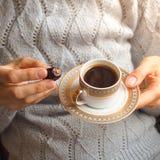 Kaffe och daterar En kopp kaffe i hennes händer med de arabiska data Royaltyfri Bild