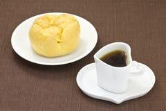 Kaffe och en kräm- puff Royaltyfri Foto