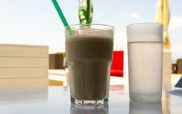 Is-kaffe och ett exponeringsglas av vatten i strandstången Royaltyfri Bild