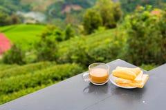 Kaffe och friterad degpinne på trätabellen på tekolonin i morgontid thailand royaltyfria foton
