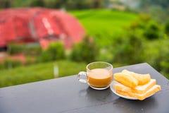 Kaffe och friterad degpinne p? tr?tabellen p? tekolonin i morgontid thailand royaltyfria foton
