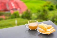 Kaffe och friterad degpinne p? tr?tabellen p? tekolonin i morgontid thailand arkivfoto