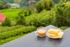 Kaffe och friterad degpinne p? tr?tabellen p? tekolonin i morgontid thailand royaltyfria bilder