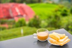 Kaffe och friterad degpinne p? tr?tabellen p? tekolonin i morgontid thailand arkivbild