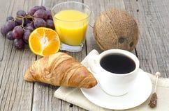 Kaffe och frukost på en trätabell Royaltyfri Fotografi