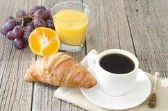 Kaffe och frukost på en trätabell Arkivbilder