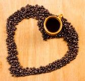 kaffe och kaffebönor som är ordnade som hjärta, formar på trä Arkivfoton