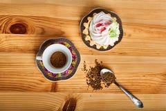 Kaffe och kaka på den bruna trätabellen Arkivbild