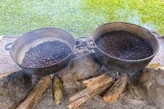Kaffe- och kakaobönor som grillar i metallhandfat med royaltyfria foton