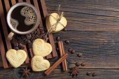 Kaffe och kakor i formen av en hjärta arkivfoton