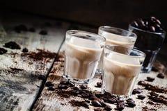 Kaffe- och krämlikör, grillade kaffebönor och malt kaffe royaltyfria foton
