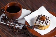 Kaffe och liten rund kaka Arkivbild