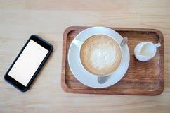 Kaffe och mjölkar på den wood tabellen med mobiltelefonen Royaltyfri Foto