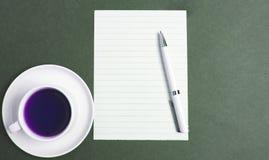 Kaffe och papper i svart bakgrund royaltyfri foto