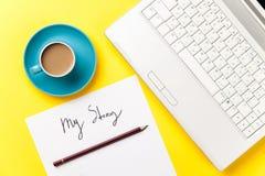 Kaffe och papper med min berättelse uttrycker nära anteckningsboken Arkivbilder