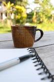 Kaffe och spiralanteckningsbok Arkivfoto