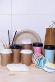 Kaffe- och tekoppar för på gå Papper och thermo rånar för varma eller kalla drinkar på trästångräknare Ljus bakgrund Royaltyfri Bild
