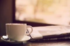Kaffe och tidningar på tabellen arkivfoto
