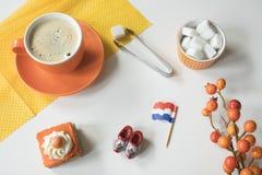 Kaffe, orange kaka, flagga och träsko för den typiska holländska händelsen Koningsdag, konungdag royaltyfria foton