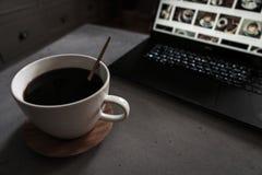 Kaffe på den konkreta tabellen med bärbara datorn som bakgrunden arkivbild