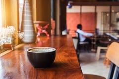 Kaffe på den wood stången i kafé med solljus royaltyfri foto