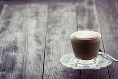 Kaffe på exponeringsglas på den wood tabellen Arkivbilder