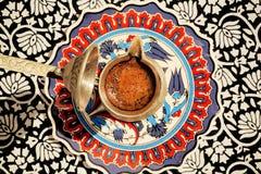 Kaffe på tabellen med det mönstrade magasinet i kafeteria Royaltyfri Foto
