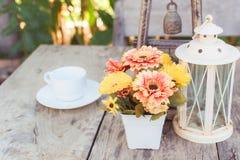 Kaffe på trätabellen med blomman Royaltyfria Bilder