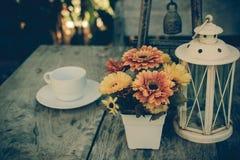 Kaffe på trätabellen med blommatappningstil Royaltyfri Bild