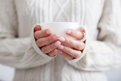 Kaffe rånar i kvinnliga händer Arkivfoto