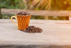 Kaffe rånar kaffebönan på trä Fotografering för Bildbyråer