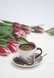 Kaffe rånar på vita bakgrund och tulpan Royaltyfri Foto
