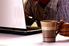 Kaffe rånar rymt av en man som arbetar på en bärbar datordator i bakgrunden royaltyfri fotografi
