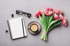 Kaffe, ren anteckningsbok, glasögon och härlig tulpanblomma på bästa sikt för stentabell i lekmanna- stil för lägenhet Funktionsd arkivfoton