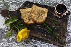 Kaffe, rostat bröd och rosor, romantisk frukost på Valentine' s-dag Tjänat som på ett träbräde med kopieringsutrymme royaltyfria bilder