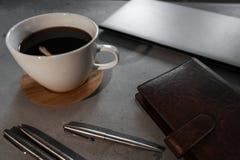 Kaffe, sked, bärbar dator, anteckningsbok och pennor på den konkreta tabellen arkivbilder