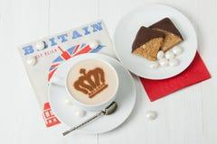 Kaffe som dekoreras med drottningkronan Pappers- servett för brittiskt symbol Arkivfoton