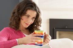 kaffe som dricker koppla av den home sofakvinnan royaltyfri bild