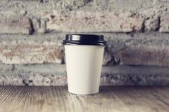Kaffe som går på en trätabell med tappningstilväggen Royaltyfri Foto