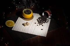 Kaffe som göras i en apelsinskal på en bambuservett Arkivfoton