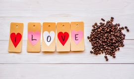 kaffe som jag älskar kaffebönor och etiketter med hjärtor på vit träbakgrund Royaltyfria Bilder