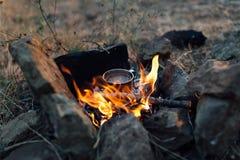 Kaffe som lagas mat över en lägereld på naturen Arkivfoton