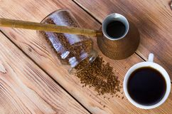 Kaffe st?r bredvid en vit kopp som fylls med varmt kaffe bland spridda kaffeb?nor, tabellen, den b?sta sikten som ?r horisontal royaltyfri foto