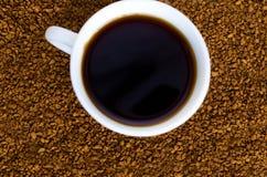 Kaffe st?r bredvid en vit kopp som fylls med varmt kaffe bland spridda kaffeb?nor, tabellen, den b?sta sikten som ?r horisontal arkivbild